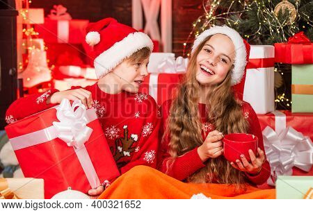 Children Little Happy Girl And Boy Find Gifts Near Christmas Tree. Gifts Shop. Kid Santa Hat Christm