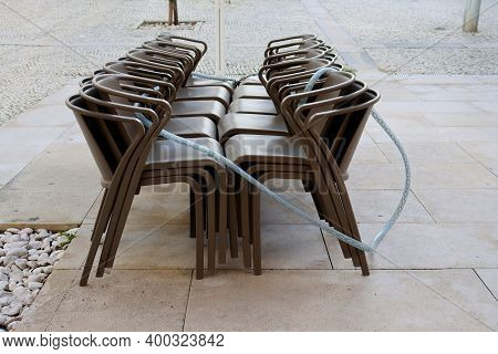 Chairs Are Stacked On Top Of Each Other In An Outdoor Cafe. The Cafe Is Closed. Cafe Without Visitor