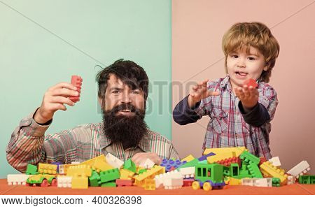 Happy Family. Father And Son Have Fun With Bricks. Child Development And Upbringing. Bearded Hipster