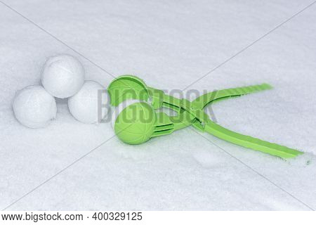 Snow Globe In The Snow. Three Snowballs Lie Next To The Device For Making Snowballs. Horizontal Phot