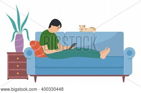 Young Man Is Lying On The Couch With A Tablet. The Guy Sits With Electronic Equipment In His Hands.