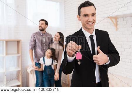 Realtor In Suit Holds Keys With Key Fob In Form Of House. Young Family Looks Apartment.