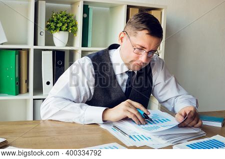 The Auditor Checks The Financial Statements Of The Company And Makes Notes On The Charts.