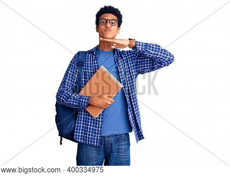 Young african american man wearing student backpack holding book cutting throat with hand as knife, threaten aggression with furious violence