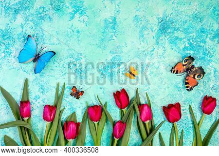 Red Tulips And Fluttering Butterflies On A Light Blue And Green Textured Background With A Copy Of S