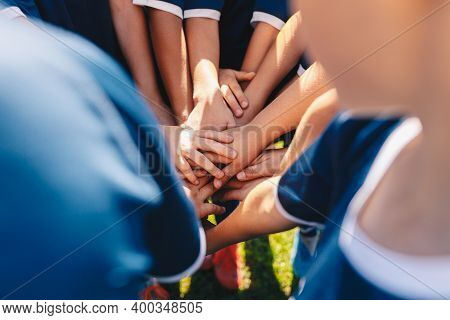Group Of Happy Children In Sports Team Stacking Hands Outdoor In A Summer Day. Children Team Sports.