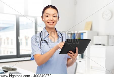 medicine, profession and healthcare concept - happy smiling asian female doctor or nurse in blue uniform with tablet pc computer and stethoscope over hospital background
