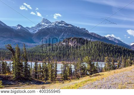 The sharp peaks of the Rocky Mountains are clearly visible against the blue sky. Stunning Abraham Lake. Great Indian summer in the Canadian Rockies.