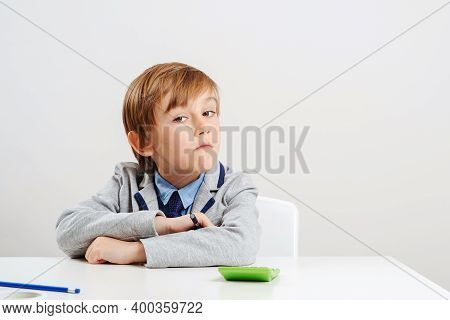 Boy In Suit Sitting At The Desk. Young Business Boy Dream About Future Profession. Education Concept
