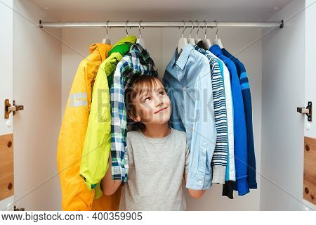 Preteen Boy Chooses Clothes In The Wardrobe Closet At Home. Kid Hiding Among Clothes In Wardrobe.