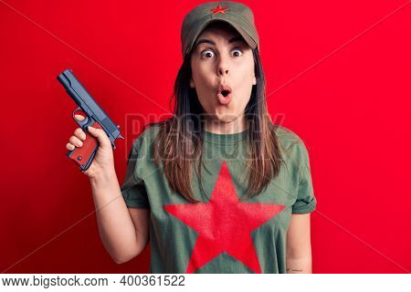 Young beautiful brunette woman wearing t-shirt with red star communist symbol holding gun scared and amazed with open mouth for surprise, disbelief face