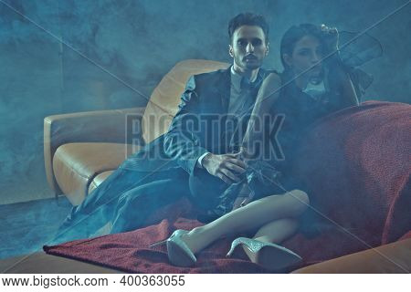 Beautiful elegant couple in fashionable evening clothes relaxing on a leather sofa in a luxury apartment. Glamorous lifestyle. Fashion shot.