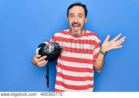 Middle age handsome motorcyclist man holding moto helmet over isolated blue background celebrating achievement with happy smile and winner expression with raised hand