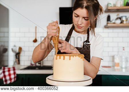 Camera footage of focused baker woman making cake with cream in kitchen