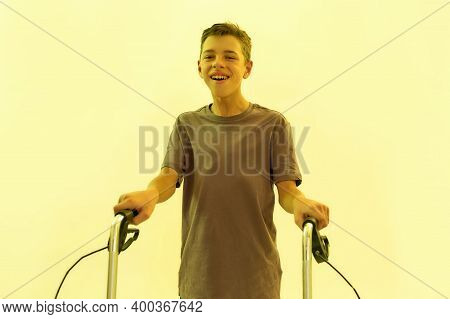 Cheerful Teenaged Disabled Boy With Cerebral Palsy Smiling At Camera, Taking Steps With His Walker I