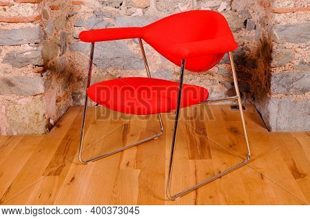 Comfortable And Stylishly Designed Red Office Chair In Front Of A Wall