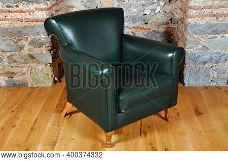 Comfortable And Stylishly Designed Green Office Chair In Front Of A Wall