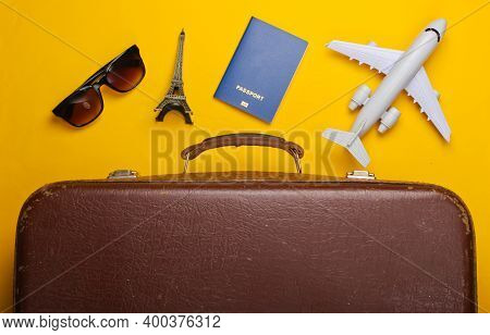 Travel Concept. Old Luggage And Travel Accessories, Souvenirs On Yellow Background. Flight Voyage, T