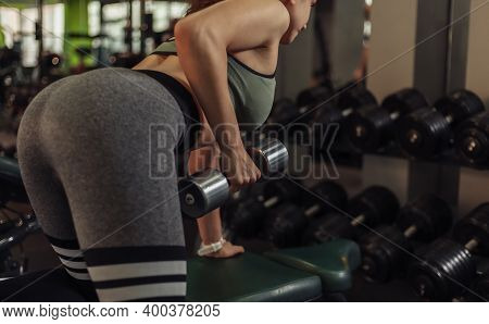 Sexy Young Fit Woman With Sportswear Doing Lifting  Dumbbell Exercise With One Hand While Leaning On