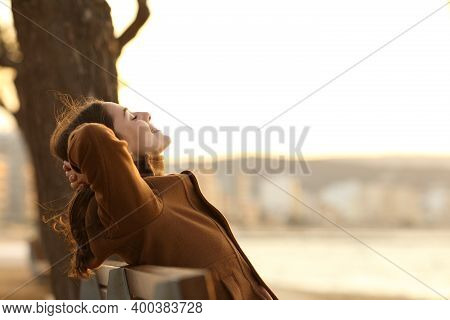 Profile Of A Woman Resting Sitting On A Bench On The Beach In Winter At Sunset