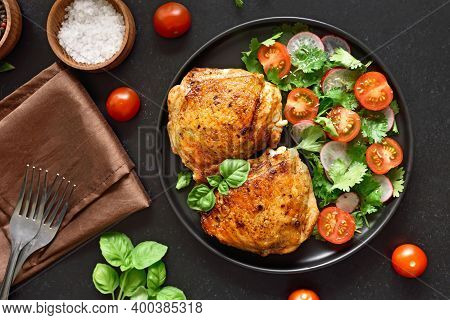 Fried Chicken Thighs With Vegetables In Plate Over Black Stone Background. Top View, Flat Lay