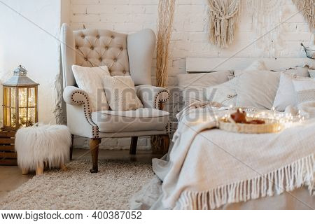 Comfortable Bedroom With Cushions On Armchair Standing Near Bed And Home Decor In Boho Chic Style. E