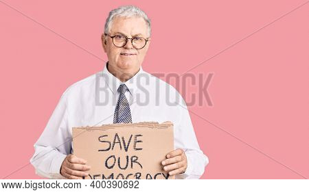 Senior grey-haired man wearing business clothes holding save our democracy protest banner looking positive and happy standing and smiling with a confident smile showing teeth