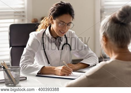 Female Doctor Write Prescription To Elderly Patient