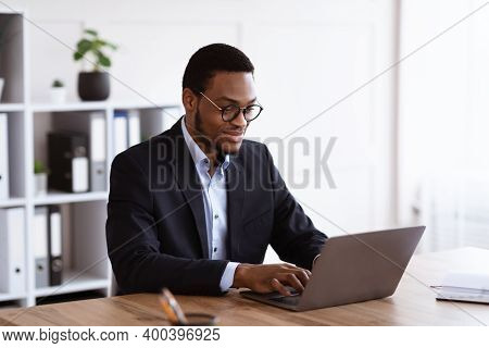 Cheerful Young Black Entrepreneur In Formal Suit Working With Laptop, Wearing Glasses, Office Interi