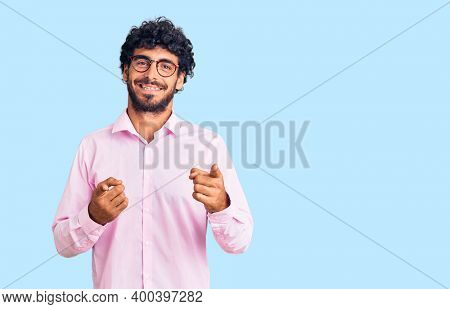 Handsome young man with curly hair and bear wearing business clothes pointing fingers to camera with happy and funny face. good energy and vibes.