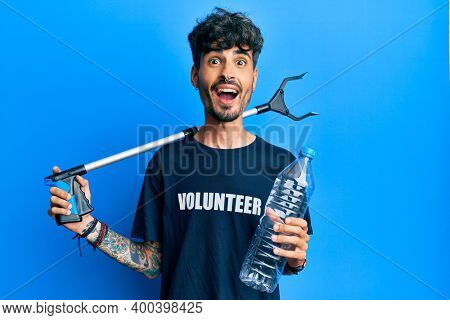 Young hispanic man holding plastic bottle and litter picker to recycle celebrating crazy and amazed for success with open eyes screaming excited.