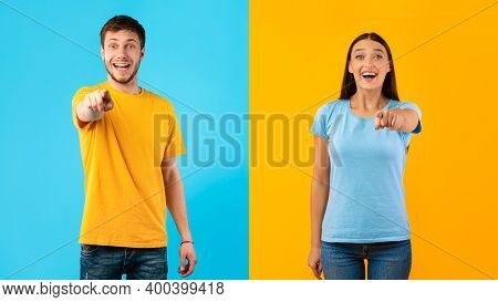 We Choose You. Portrait Of Excited Young Man And Woman Pointing Fingers At Camera, Standing Isolated