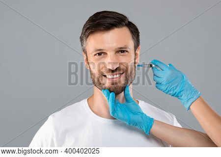 Cosmetician Hands In Protective Gloves Injecting Face Filler For Middle-aged Man Over Grey Studio Ba