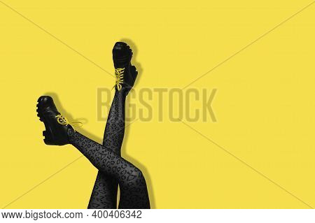 New Gray Female Boots On Long Slender Crossed Woman Legs In Gray Tights Isolated On Yellow Backgroun
