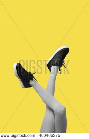 New Black Female Sneakers On Long Slender Woman Legs In Gray Tights Isolated On Yellow Background. C