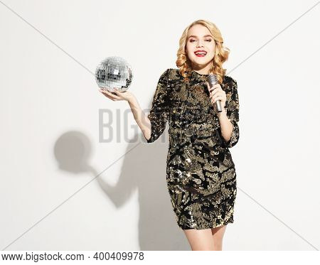 Party and celebration concept: Young blond woman with long curly hair dressed in evening dress holding a microphone and disco ball, singing and smiling