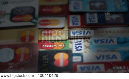 Ray Of Light Falling To Credit Cards With Visa And Mastercard Brand Logo. Close Up Of Many Visa And