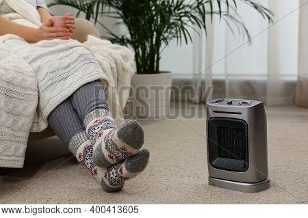 Woman Warming Legs Near Halogen Heater At Home, Closeup