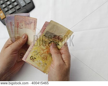 Hands Of A Woman Counting Brazilian Banknotes And Calculator On The Table