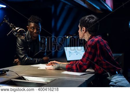 Black Guy Chooses A Tattoo Sketch In A Tattoo Studio. He Is Helped By A Young Pretty Administrator T