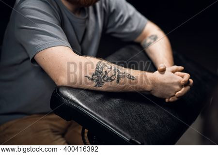 Close-up Of A Mans Hands With A Snake Tattoo On A Leather Tattoo Table In A Tattoo Parlor
