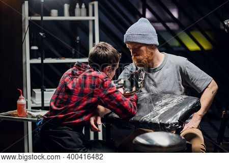An Experienced Tattoo Artist Gives A Tattoo To A White Scandinavian Hipster Man With A Red Beard In