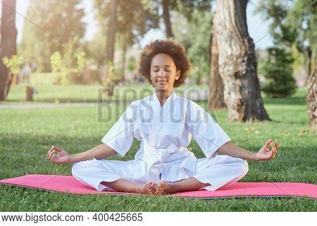 Cute Afro American Girl In Karate Kimono Meditating Outdoors