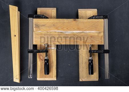 Gluing Pieces Of Wood With Carpentry Glue. Boards In Carpentry Clamps.