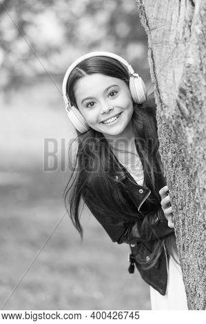 Baby Tech. Happy Child Wear Headphones Outdoors. Small Girl Listen To Music In Headphones. Protectin