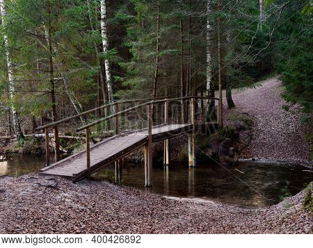 A Wooden Bridge Over A Forest Stream