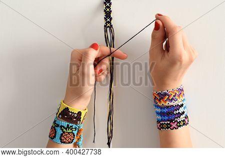 Process Of Weaving Knot For Diy Friendship Bracelet. Female Hands With Many Handmade Bracelets On Wr