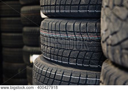 Stack Of New Tires Sale At The Auto Shop. Pile Of Tires In Stock.
