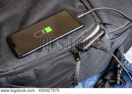 Close-up Of Charging A Smartphone From A Power Bank. The Phone Is On The Backpack, And The Power Ban