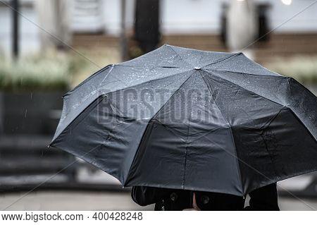 A Man Hides Under An Umbrella From The Rain. Black Umbrella Close Up.